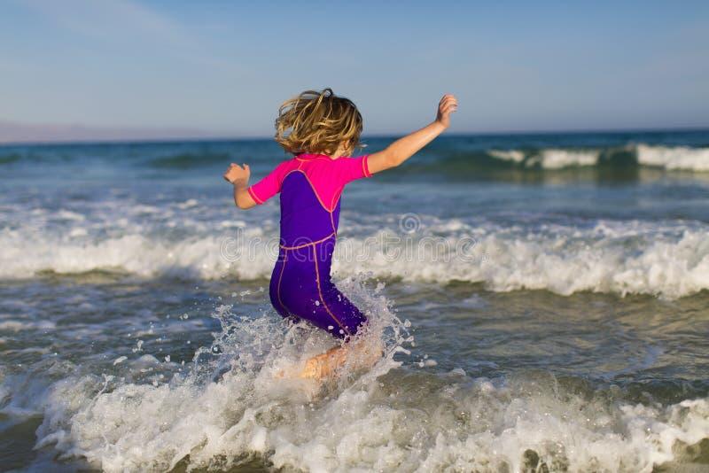 Het gelukkige meisje spelen in de golven stock afbeeldingen