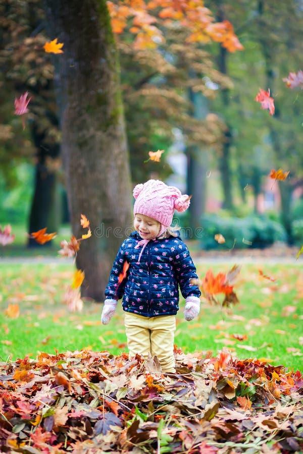 Het gelukkige meisje spelen met bladeren stock fotografie