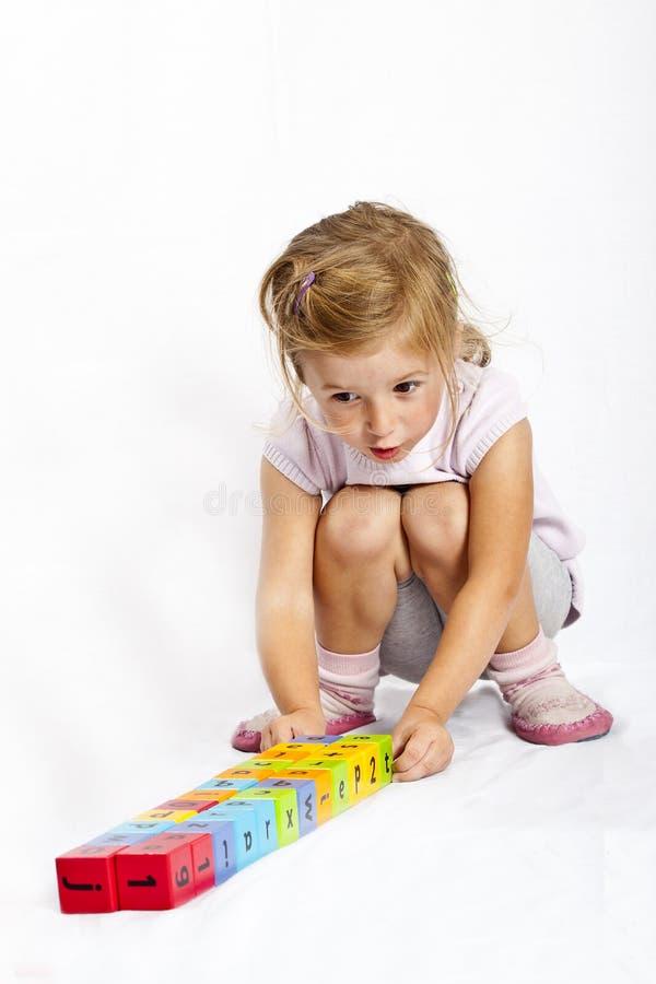 Het gelukkige meisje spelen met kleurrijke houten blokken royalty-vrije stock afbeelding