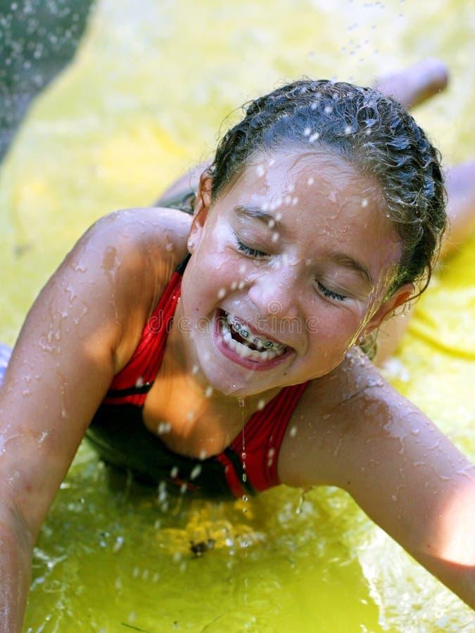 Het gelukkige meisje spelen met water stock afbeelding