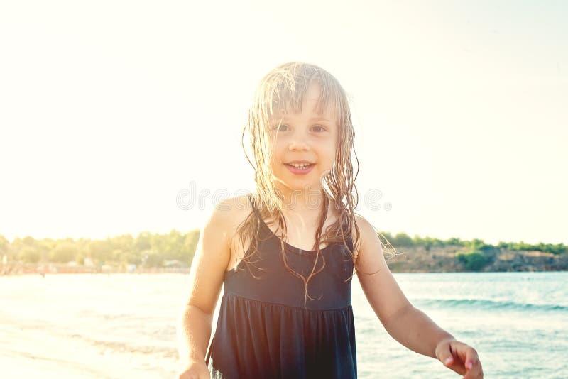 Het gelukkige meisje spelen op overzees strand stock afbeeldingen