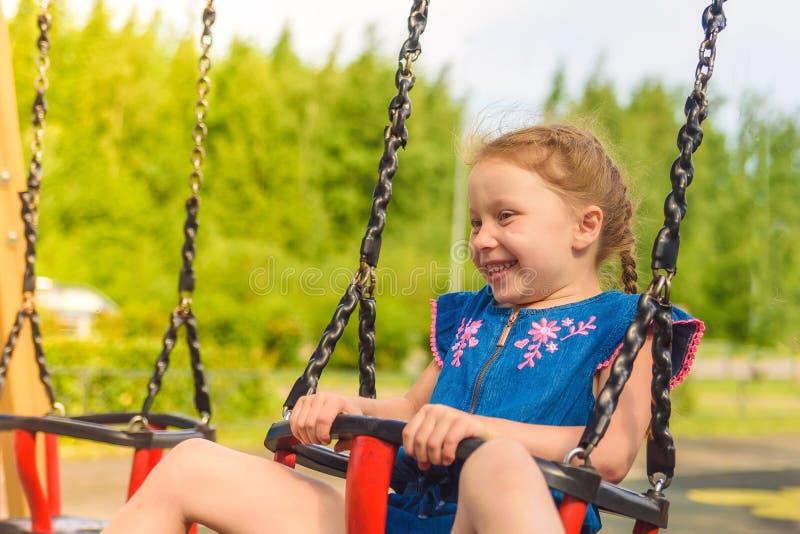 Het gelukkige meisje spelen, het uitgaan advertentie neer op een geschommel op een grasrijke speelplaats in onbeschadigde aard on stock afbeeldingen