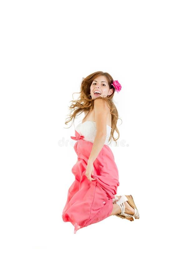 Het gelukkige meisje springen van vreugde in roze kleding met bloem stock fotografie