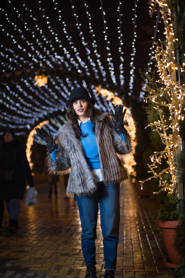 Het gelukkige meisje stellen met de winterlichten op de achtergrond royalty-vrije stock foto