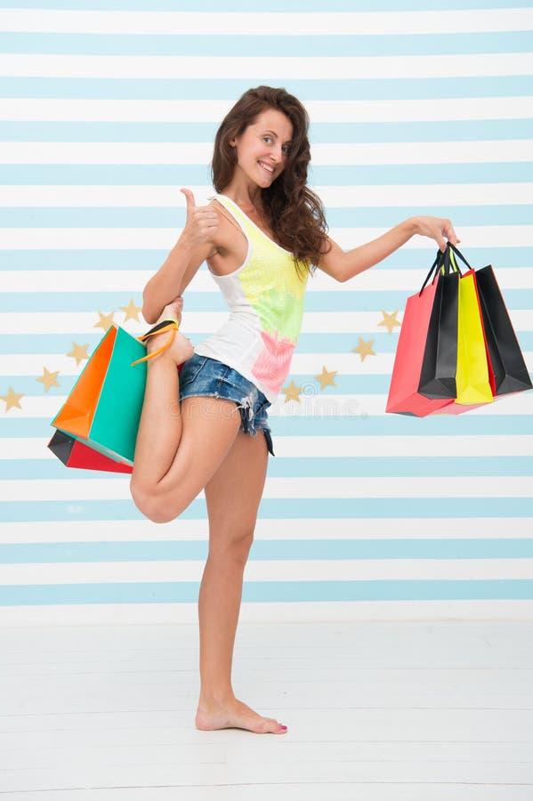 Het gelukkige meisje toont duim voor het winkelen voordeel Gelukkig meisje met het winkelen zakken verkoopvoordeel en speciale aa stock foto's