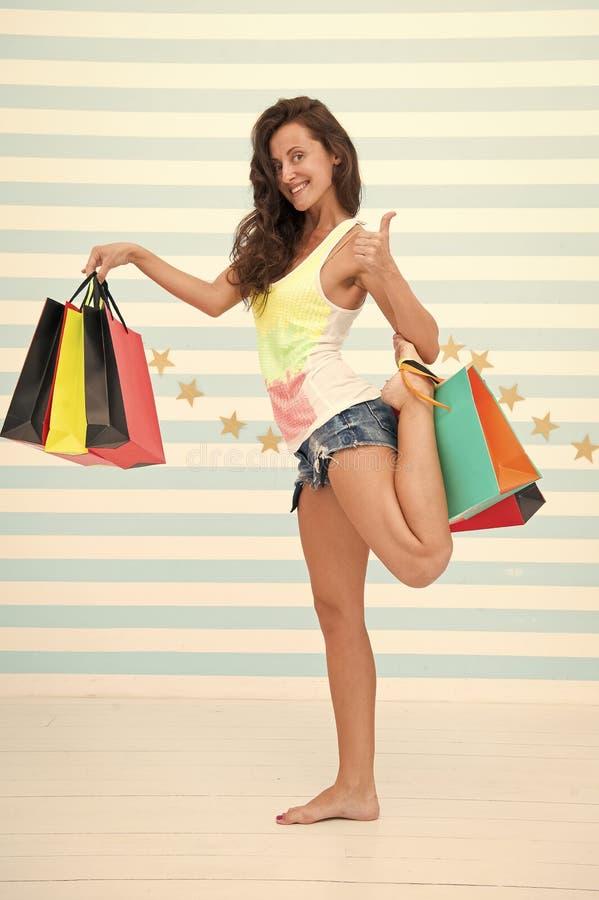 Het gelukkige meisje toont duim voor het winkelen voordeel Gelukkig meisje met het winkelen zakken verkoopvoordeel en speciale aa stock foto