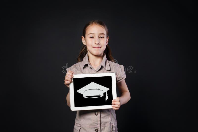 Het gelukkige meisje toont het scherm van Digitale Tablet met graduatie GLB royalty-vrije stock foto