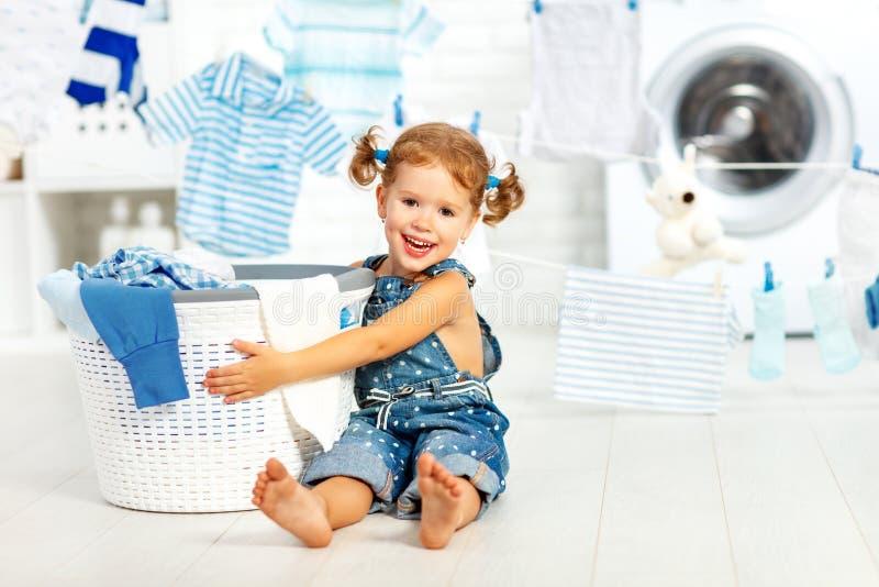 Het gelukkige meisje van de kindpret om kleren in wasserijruimte te wassen stock afbeeldingen