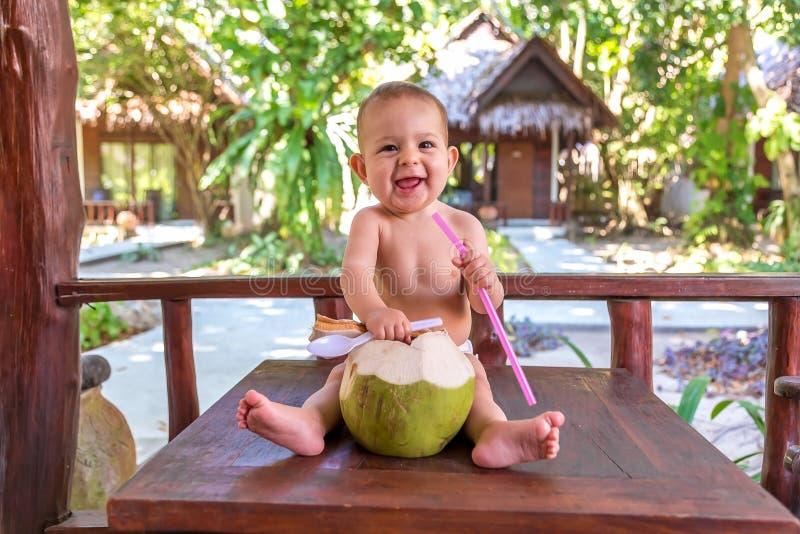 Het gelukkige meisje van de zuigelingsbaby bij tropische vakantie Eet en drinkt groene jonge kokosnoot Zit op een houten lijst royalty-vrije stock afbeeldingen