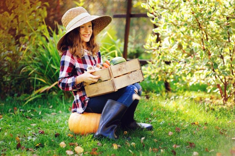 het gelukkige meisje van het landbouwerskind met de herfstoogst - organische pompoenen, wortelen en zuccini stock foto's