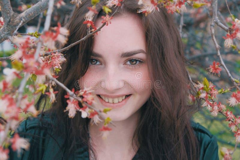 Het gelukkige meisje verbergt haar het glimlachen gezicht in takken van bloeiende kers van abrikoos stock foto's