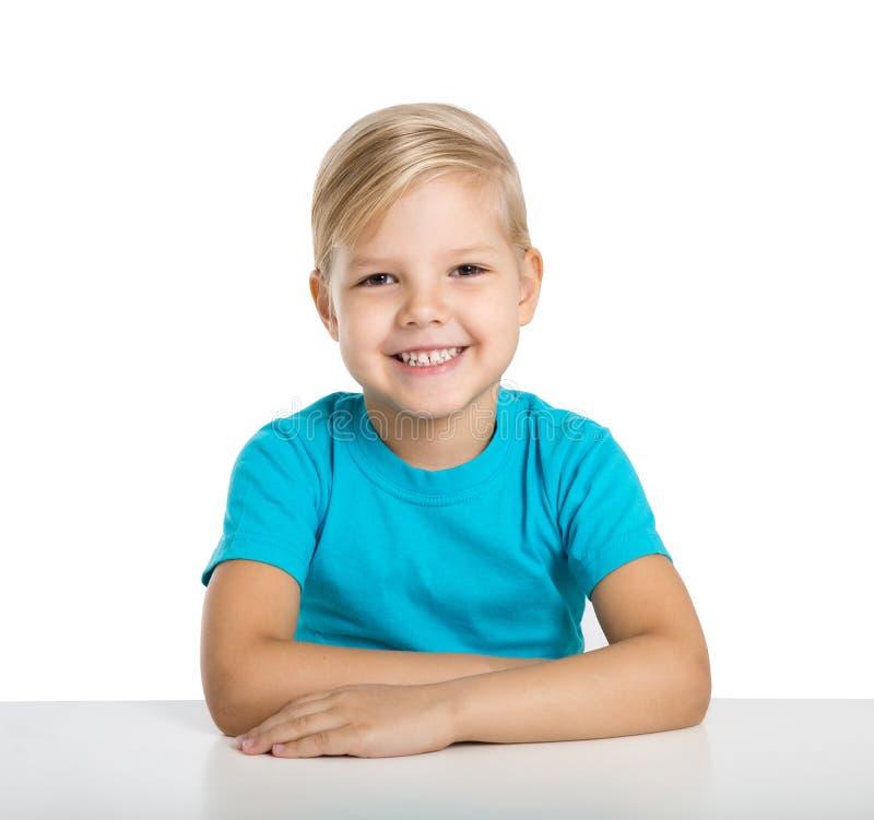 Het gelukkige meisje zit bij een lijst en een glimlach stock afbeelding