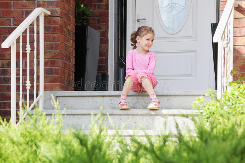 Het gelukkige meisje zit op treden dichtbij deur, glimlacht royalty-vrije stock afbeeldingen