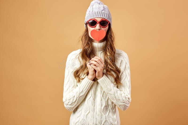 Het gelukkige meisje in zonnebril kleedde zich in witte gebreide sweater en hoedenrijkenpret met een rood document hart op een st royalty-vrije stock foto