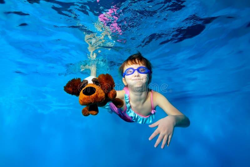 Het gelukkige meisje zwemt onderwater in de pool, het houden van een stuk speelgoed hond in hand, het bekijken camera en het glim stock foto's