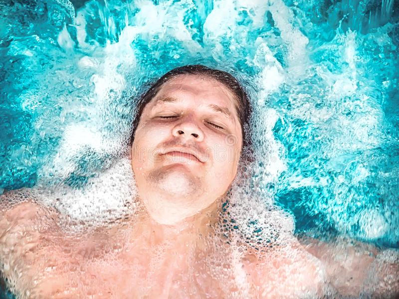Het gelukkige mens ontspannen in de Jacuzzi en het sluiten van zijn ogen Het Kaukasische jongen rusten in een pool ligt in water  stock foto's