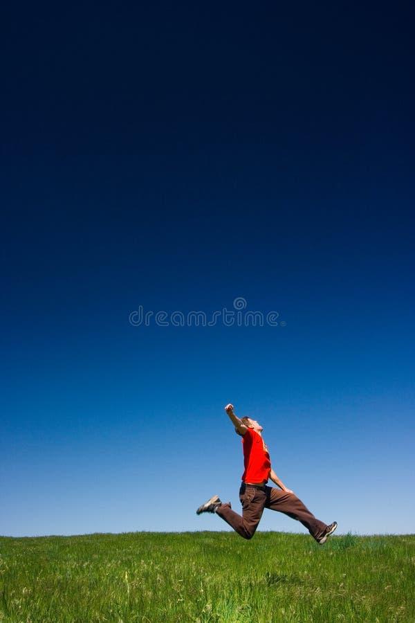 Het gelukkige mens springen stock foto's