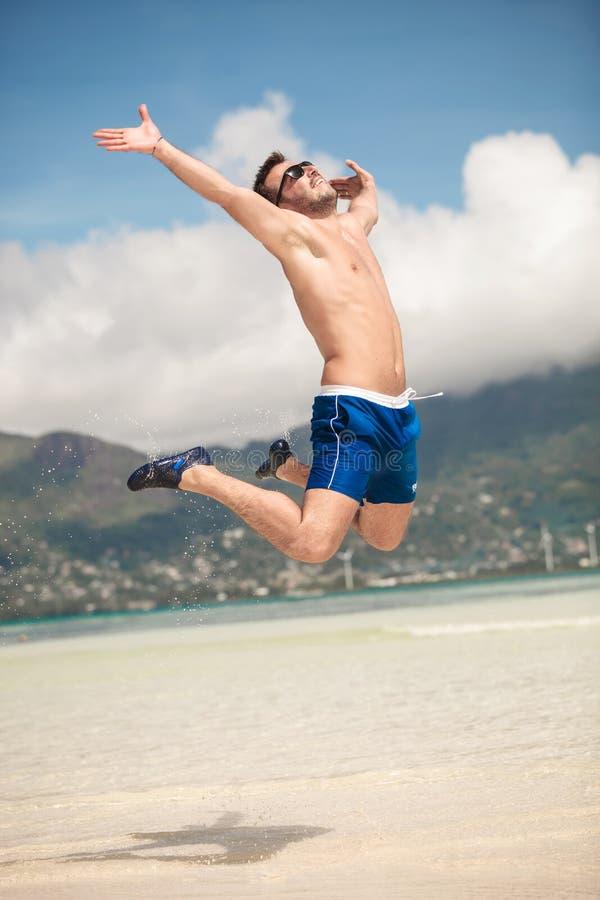 Het gelukkige mens springen van vreugde op het strand royalty-vrije stock afbeeldingen