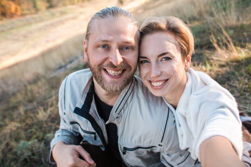 Het gelukkige middenleeftijdspaar maakt in openlucht selfie royalty-vrije stock afbeelding