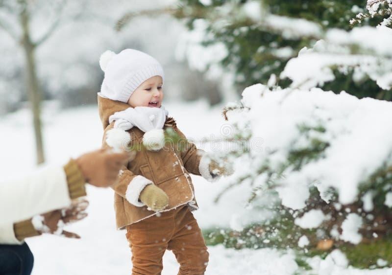 Het gelukkige moeder en baby spelen met sneeuw op tak royalty-vrije stock fotografie