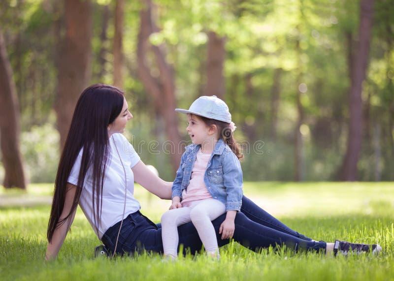 Het gelukkige moeder en dochter ontspannen in het park De scène van de schoonheidsaard met familie openluchtlevensstijl in de le stock foto's