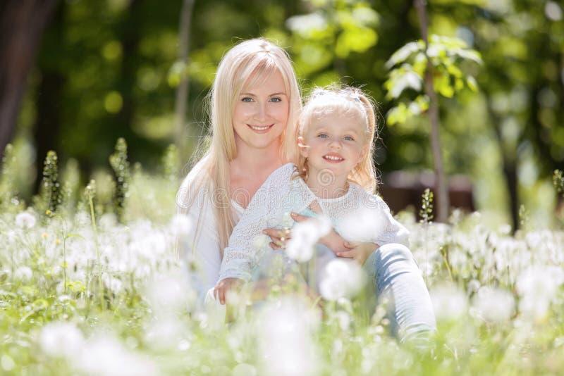 Het gelukkige moeder en dochter ontspannen in het park De sc?ne van de schoonheidsaard met familie openluchtlevensstijl in de len stock afbeelding