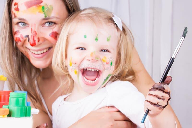 Het gelukkige moeder en dochter schilderen stock foto