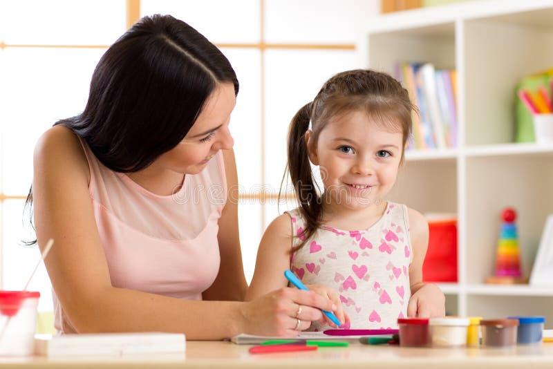 Het gelukkige moeder en jong geitjedochter schilderen met potloden royalty-vrije stock foto's