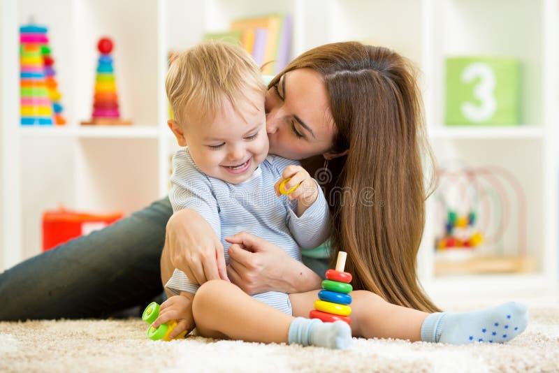 Het gelukkige moeder en kindzoon binnen spelen thuis stock afbeelding