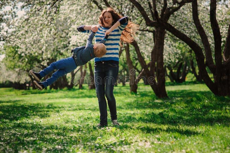Het gelukkige moeder en peuterzoon spelen openlucht in de lente of de zomerpark royalty-vrije stock foto