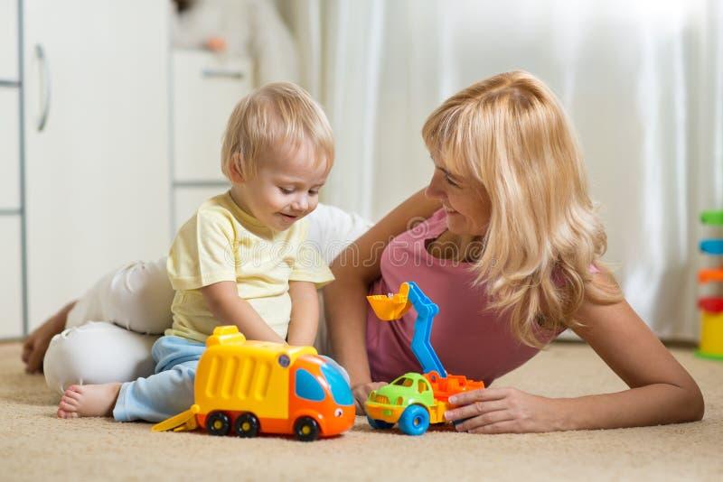 Het gelukkige moeder spelen met babyjongen thuis stock fotografie