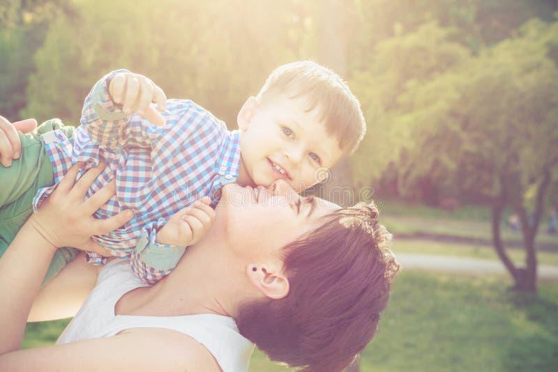 Het gelukkige moeder spelen met haar peuterzoon in park stock foto's