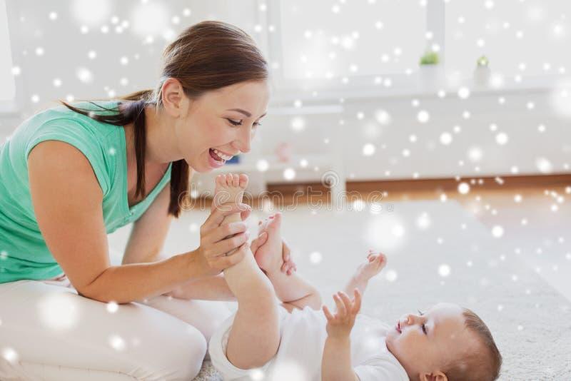 Het gelukkige moeder spelen met weinig baby thuis stock afbeeldingen