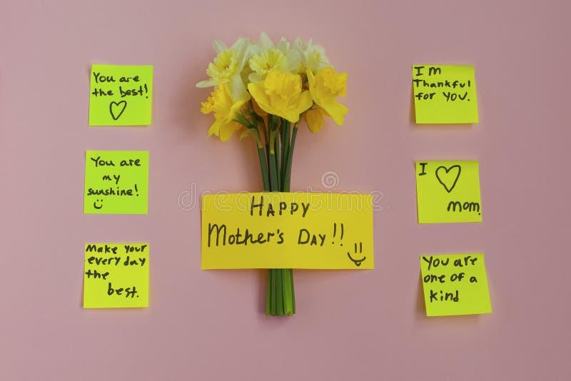 Happy Mother's Day bouquet van daffodils en noteer de gele sticker op het bureau royalty-vrije stock fotografie