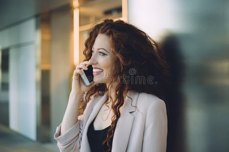 Het gelukkige mooie jonge roodharigevrouw doen winkelend en sprekend royalty-vrije stock foto's