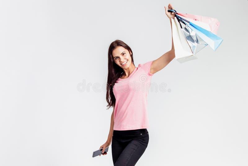 Het gelukkige mooie meisje gekleed in roze t-shirt en jeans houdt het winkelen zakken en telefoon in haar handen op het wit stock afbeelding
