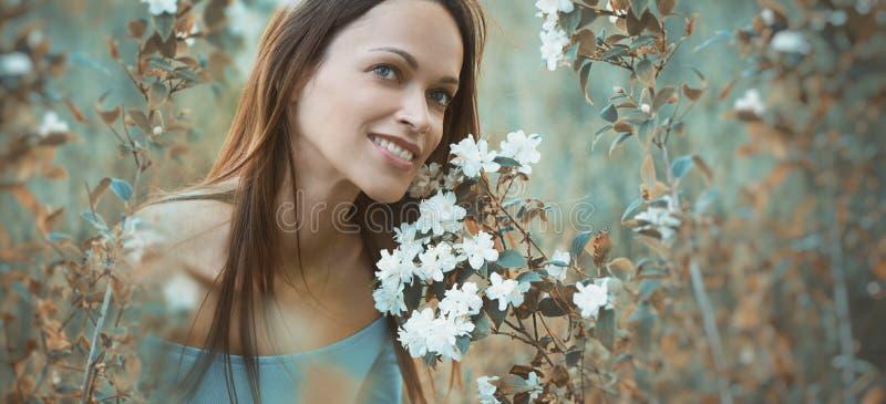 Het gelukkige mooie meisje zit op groen gras royalty-vrije stock fotografie