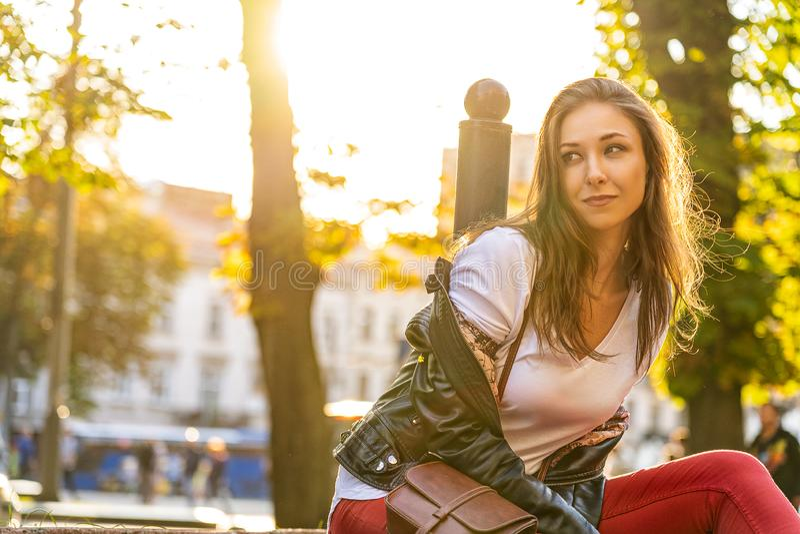 Het gelukkige mooie meisje zit in openlucht en glimlacht Levensstijlfotografie met jong vrouwelijk model met backlightzon royalty-vrije stock fotografie