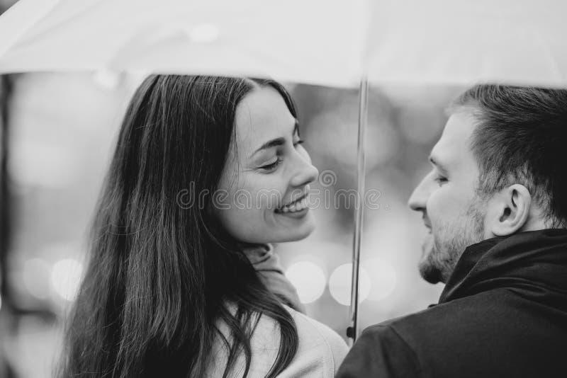 Het gelukkige mooie paar, de kerel en zijn meisje kleedden zich in vrijetijdskledingstribune onder de paraplu en bekijken elkaar stock afbeeldingen