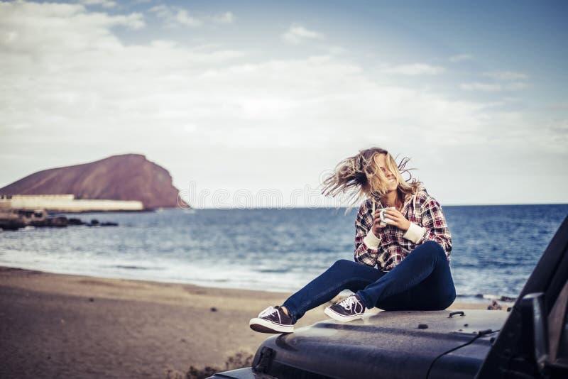 Het gelukkige mooie verblijf van het blonde jonge meisje openlucht genietend van het weer en van de reis met van weg zwarte auto  stock foto's
