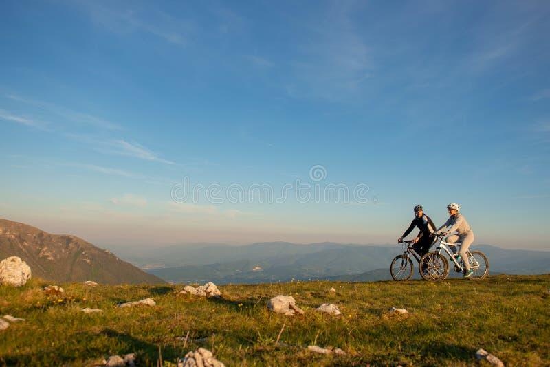 Het gelukkige mountainbikepaar heeft samen in openlucht pret op een zonsondergang van de de zomermiddag stock foto's