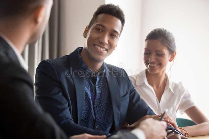 Het gelukkige multiraciale paar raadplegen op specialistenkantoor stock foto's