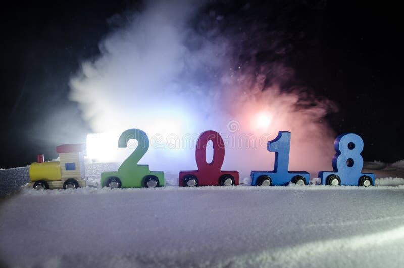 het gelukkige nieuwe jaar van 2018, houten stuk speelgoed trein het dragen aantallen van het jaar van 2018 op sneeuw Stuk speelgo stock foto's