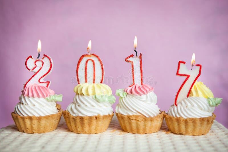 Het gelukkige nieuwe jaar van 2017 met kaarsen op cakes met roze achtergrond stock foto's