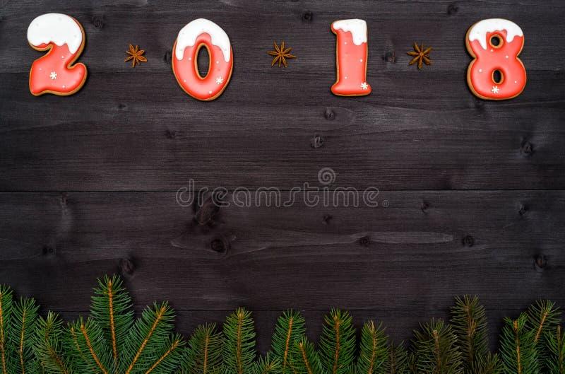 Het gelukkige nieuwe symbool van het jaar 2018 teken van rode en witte peperkoekkoekjes op donkere houten achtergrond met spar ve royalty-vrije stock afbeeldingen