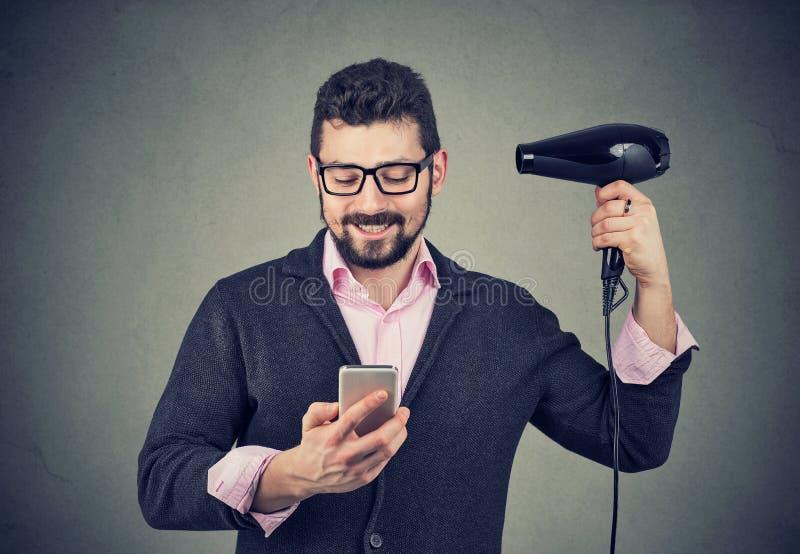 Het gelukkige nieuws van de mensenlezing op smartphone blazend haar met hairdryer stock afbeeldingen