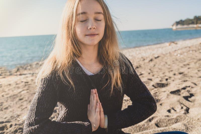 Het gelukkige ontspannen jonge vrouw mediteren in een yoga stelt bij het strand stock foto's