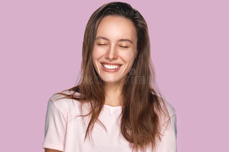 Het gelukkige opgetogen wijfje met positieve glimlach, glimlachen ruim, kleedde zich in toevallige die kleding, over lavendelmuur royalty-vrije stock fotografie
