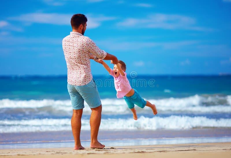 Het gelukkige opgewekte vader en zoons spelen op de zomerstrand, geniet van het leven stock afbeelding