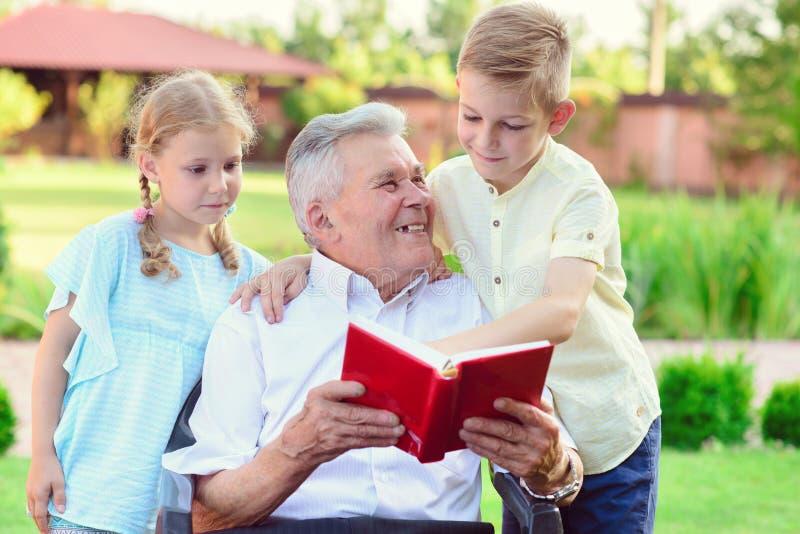 Het gelukkige oude boek van de grootvaderlezing voor leuke kinderen in tuin stock fotografie